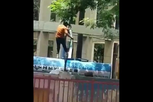 Water Tanker driver cleans his legs while standing upon the tanker