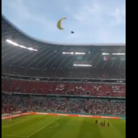 A Greenpeace activist lands at Allianz Arena with a parachute prior to the match between France and Germany in Munich