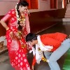 Groom takes blessings from wife