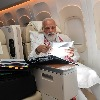 Modi busy on flight to US photo goes viral